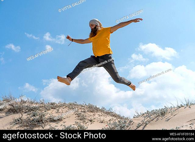 Carefree man with arms outstretched jumping on sand at beach