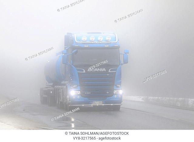 Salo, Finland - December 28, 2018: Blue Scania R580 tank truck moving along wintery highway on a very foggy day in South of Finland