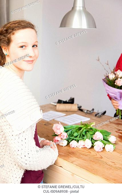 Portrait of teenage girl buying roses in florists