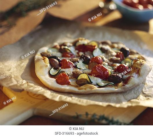 Pizza topped with merguez sausage and black olives