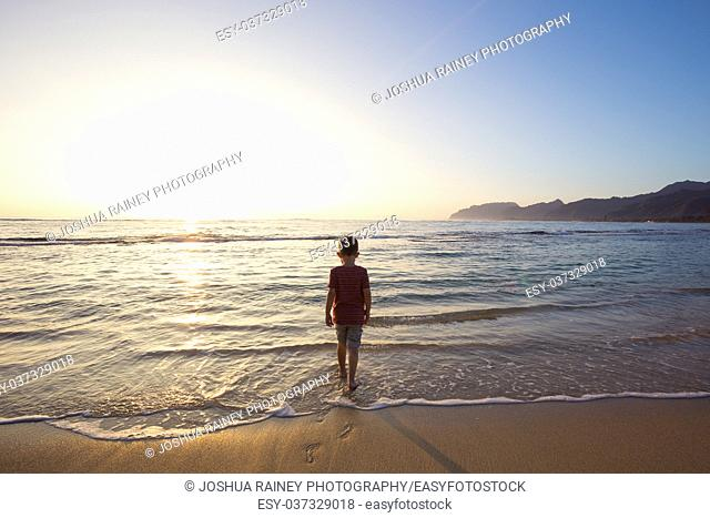 Five year old young boy playing in the water of the Pacific Ocean at sunrise in Oahu Hawaii while on vacation