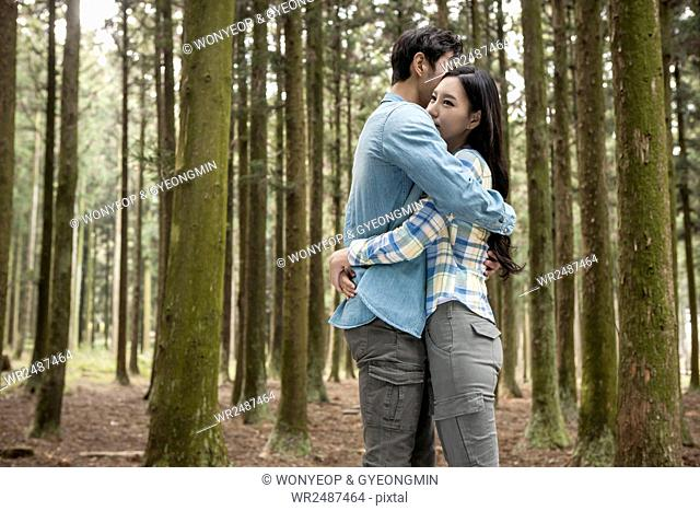 Side view of young smiling couple standing hugging each other in forest