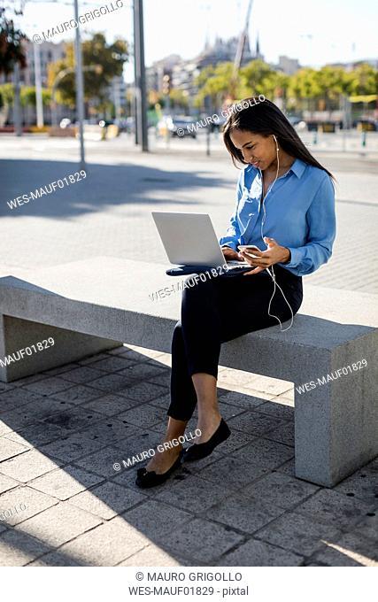 Businesswoman using laptop, holding smartphone