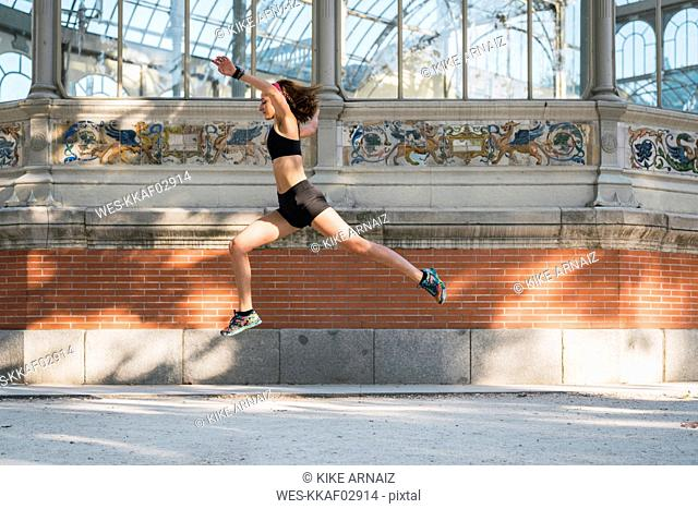 Fit young woman running an jumping in park