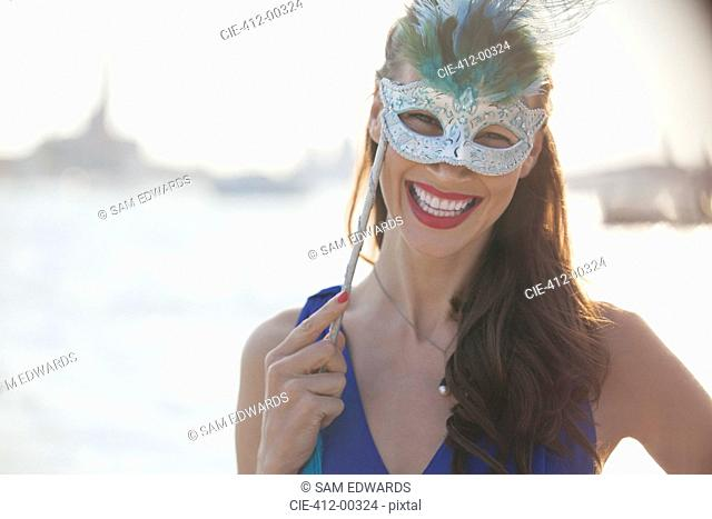 Portrait of smiling woman wearing mask at waterfront in Venice