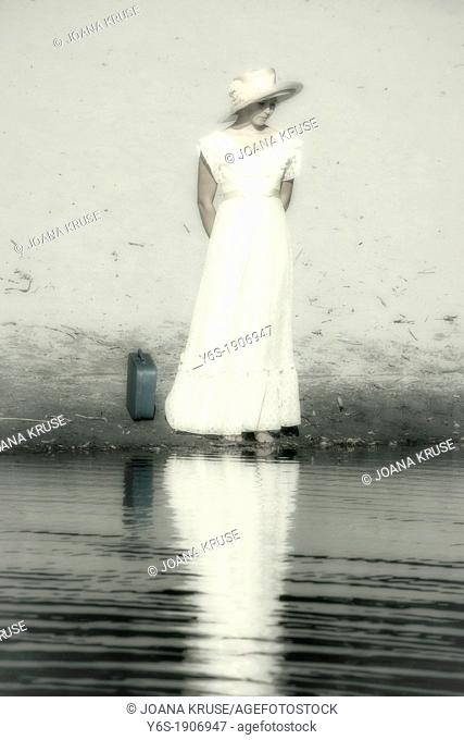 a woman in a yellow dress is standing at a pond with a suitcase