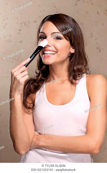 Young woman holding cosmetic paint brush on her nose