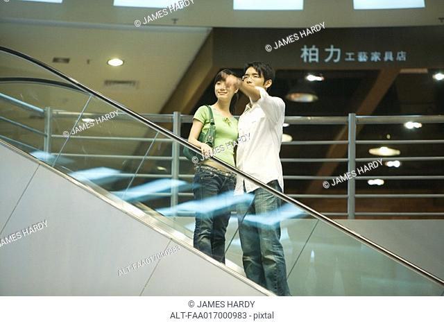 Couple taking escalator in shopping mall, man pointing out of frame