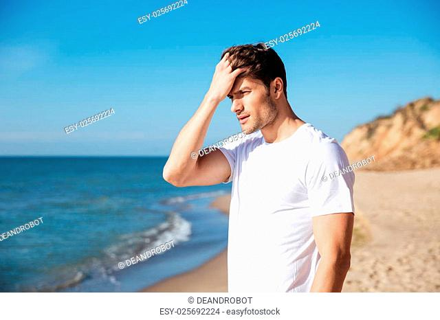 Serious attractive young man standing on the beach