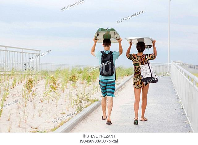 Rear view of young couple carrying surfboards on heads, Rockaway Beach, New York State, USA