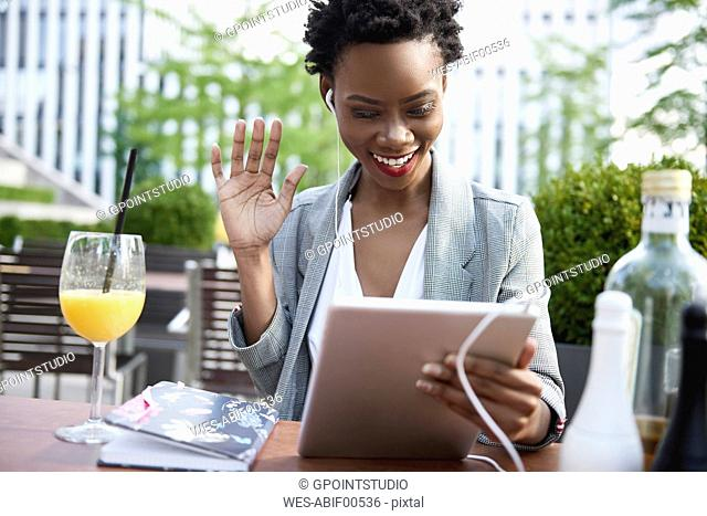Portrait of smiling businesswoman having video conference with digital tablet at sidewalk cafe