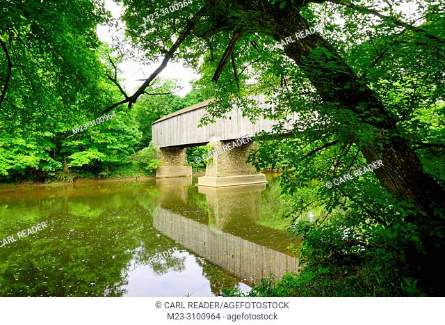 A stream flows under an old wooden covered bridge surrounded by lush foliage, Pennsylvania, USA