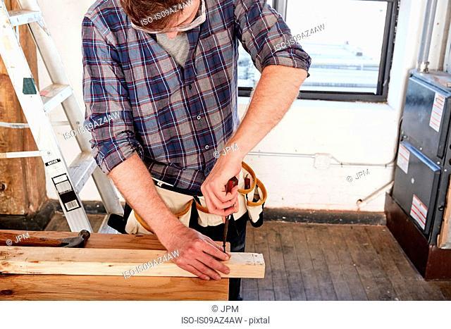 Carpenter in workshop screwing timber
