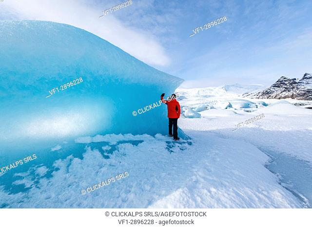 Fjallsarlon glacier lagoon, East Iceland, Iceland. Man with red coat admiring the view of the frozen lagoon in winter (MR)
