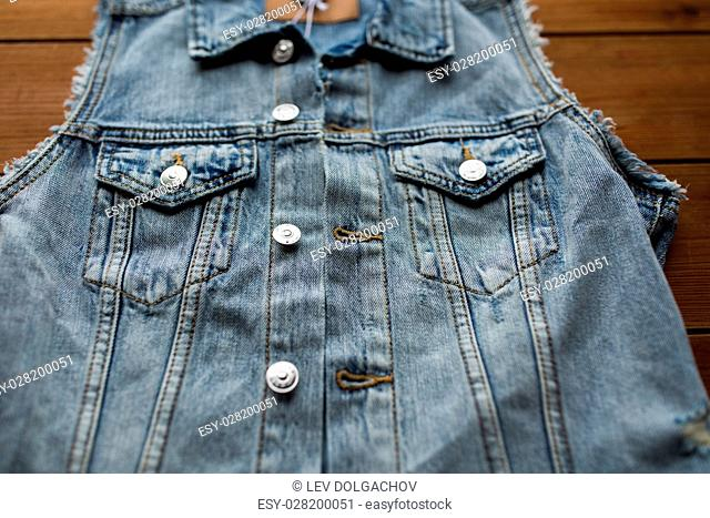 clothes, wear and fashion concept - close up of denim vest or waistcoat on wooden background