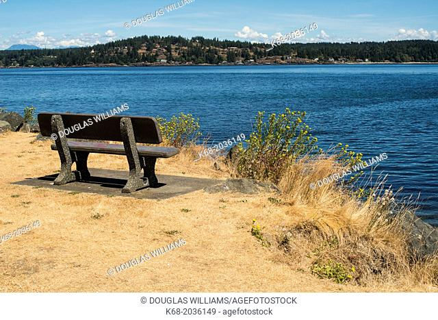 a bench in Robert V. Ostler Park in Campbell River, BC, Canada with a view toward Quadra Island