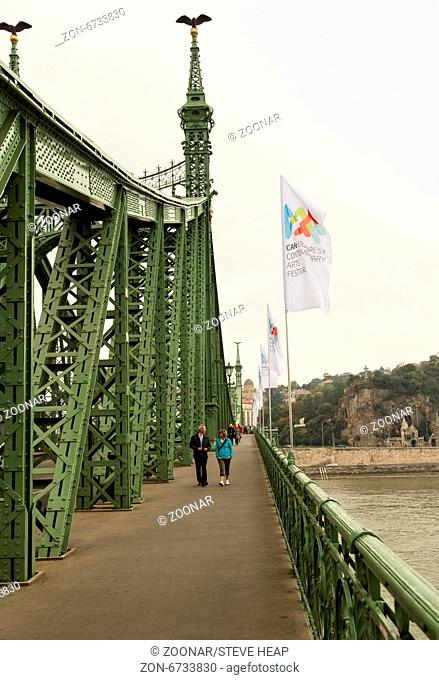 Tourists walking across the restored Liberty or Freedom Bridge across the River Danube in Budapest, Hungary