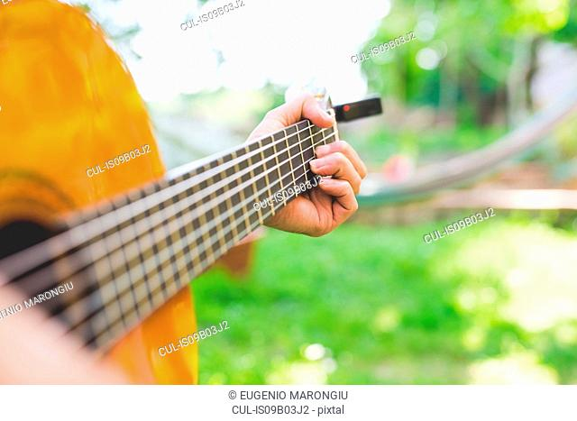 Man's hands playing acoustic guitar in garden