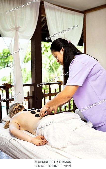 Woman having hot stone massage in spa