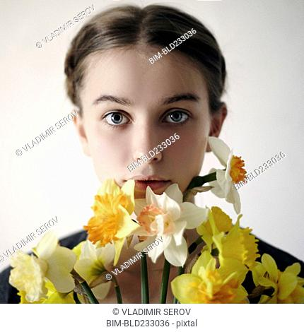 Serious Caucasian girl holding flowers on face