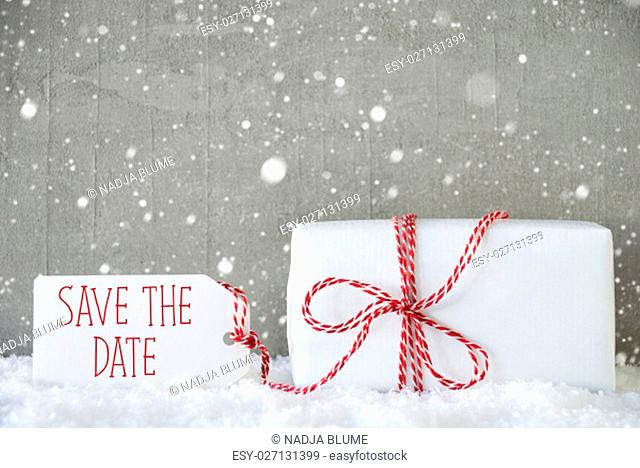 Label With English Text Save The Date. One Christmas Present On Snow. Cement Wall As Background With Snowflakes. Modern And Urban Style