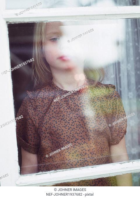 Girl looking through window, Smaland, Sweden
