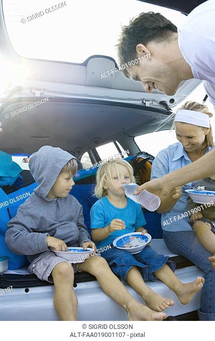 Children eating meal in back of car