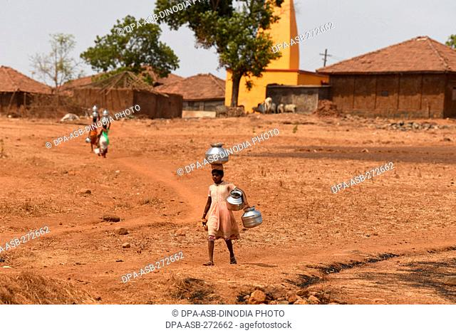 Young girl carrying pots to collect water from well at Mal village, Thane, Maharashtra, India, Asia