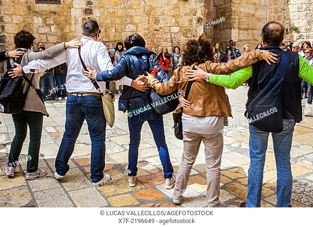 Pilgrims following Jesus' steps on the Via Dolorosa, in exterior of Church of the Holy Sepulchre also called the Church of the Resurrection, Christian Quarter
