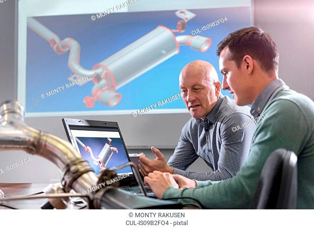 Engineers discussing CAD drawings onscreen of exhaust system in factory