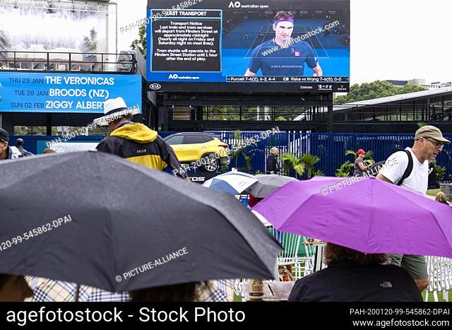 20 January 2020, Australia, Melbourne: Tennis: Grand Slam, Australian Open. Spectators sit with umbrellas in front of a video screen