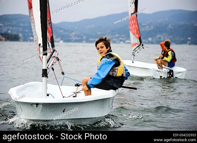 Child sailing on sailboat in the waters of Lake Maggiore, Ispra, Varese, Lombardy, Italy ¡