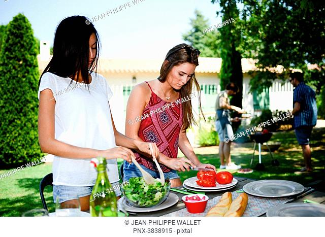 Two beautiful young woman in the garden preparing tomato salad for barbecue party during summer holiday