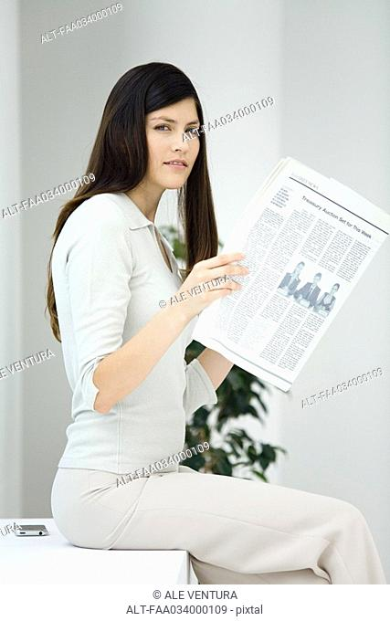 Business woman sitting, holding newspaper, looking at camera