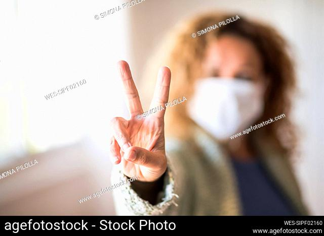 Woman with face mask making victory sign