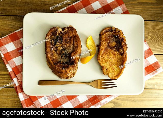 typical Spanish Torrijas, French toast, on a plate, a typical Spanish dessert eaten at Lent and Easter, fork and napkin on a wooden table from above