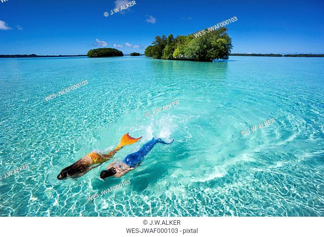 Palau, two young women in mermaid costume swimming in a lagoon