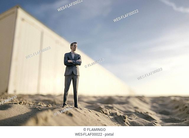 Businessman figurine standing on sand in front of building