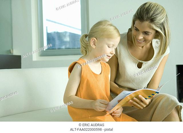Woman reading book with little girl