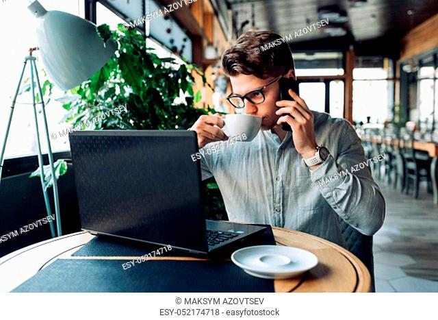Successful attractive young businessman in eyeglasses drinking coffee, during having phone conversation, looking at laptop screen. At cafe