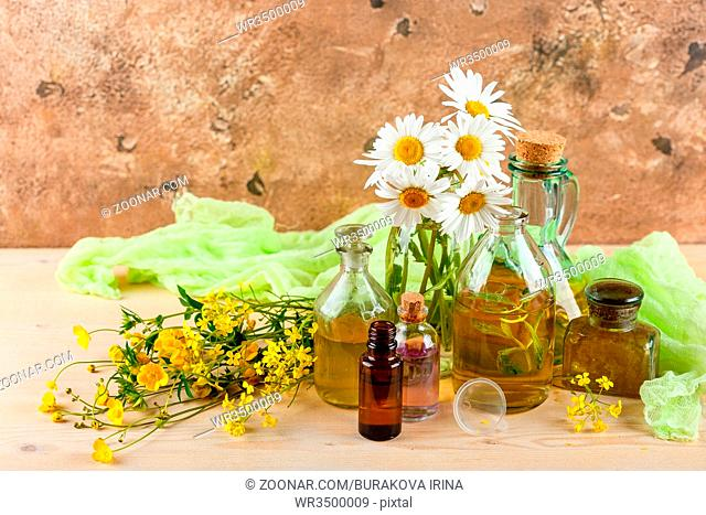 Bottles with natural aroma of essential oils, mortar and wild flowers, Spa concept. Herbal medicine