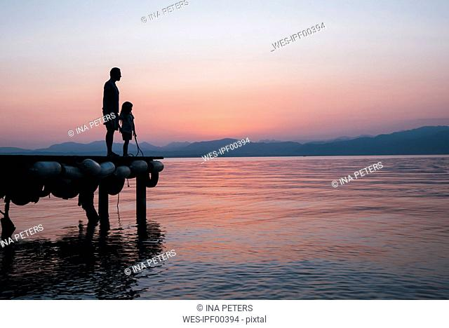 Italy, Lazise, father and little daughter standing on jetty looking at Lake Garda at sunset
