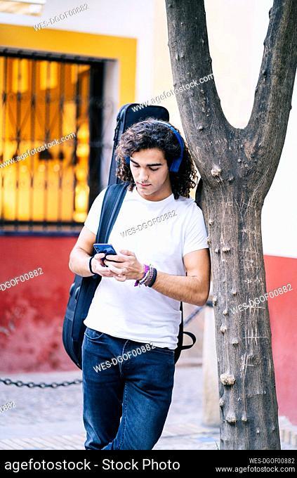 Young man using mobile phone while carrying guitar bag, Santa Cruz, Seville, Spain