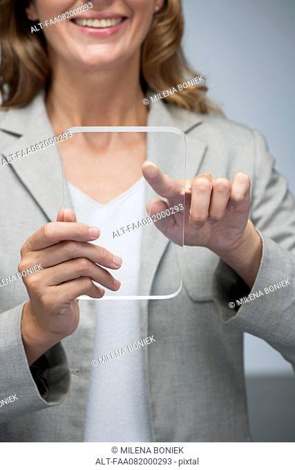 Businesswoman using transparent digital tablet