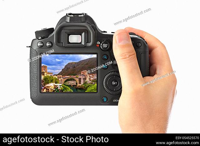 Hand with camera and Mostar - Bosnia and Herzegovina image (my photo) isolated on white background