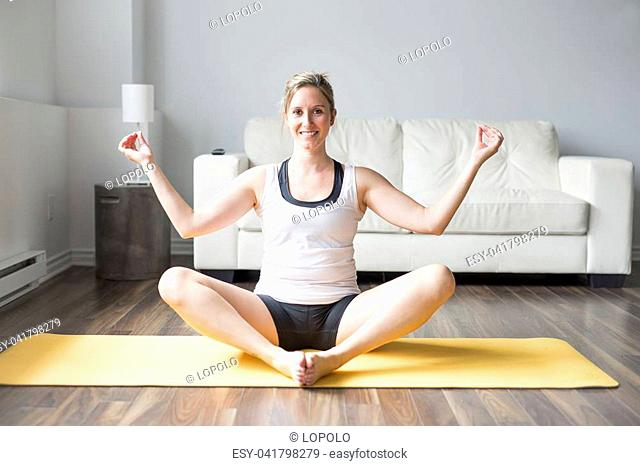 attractive young woman working out at home in living room, doing yoga or pilates exercise