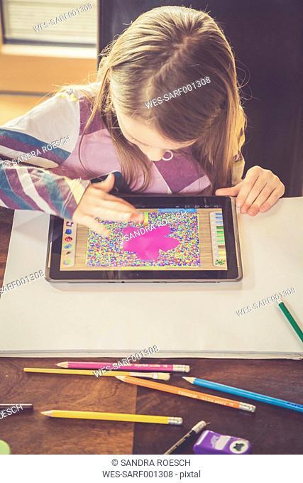 Little girl using digital tablet for drawing