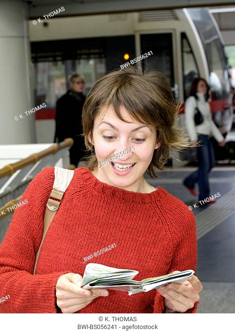 young woman / twen, reading city map, being surprised, mouth wide open, subway in the background