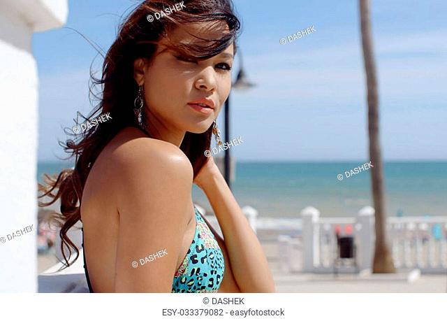 Thoughtful young woman at the seaside standing in her bikini looking at the camera close up head and shoulders showing off her cleavage