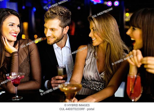 Man talking to women at bar